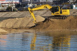 川岸で工事を行う油圧ショベルの写真素材 [FYI04818687]