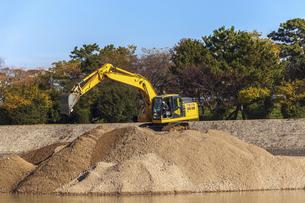 川岸の砂山の上で作業をする油圧ショベルの写真素材 [FYI04818689]