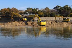 川岸で工事を行う複数の建設機械の写真素材 [FYI04818699]