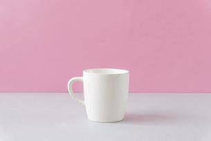 テーブルの上のマグカップとピンク色の壁の写真素材 [FYI04818896]