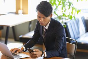 スマートフォンを確認するビジネスマンの写真素材 [FYI04819499]