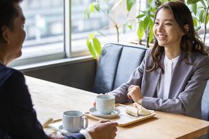 カフェで軽食をとるビジネス男女の写真素材 [FYI04819533]