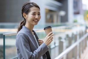 コーヒーを持つ笑顔のビジネスウーマンの写真素材 [FYI04819540]