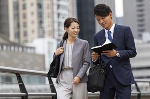 手帳を確認するビジネス男女の写真素材 [FYI04819542]