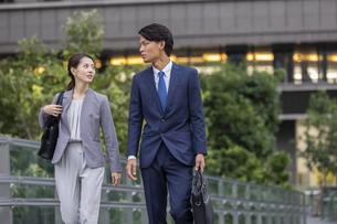 オフィス街を歩くビジネス男女の写真素材 [FYI04819546]