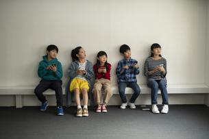 スマホを持って遠くを見る子どもたちの写真素材 [FYI04820152]