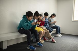 スマホにのめりこむ子どもたちの写真素材 [FYI04820153]