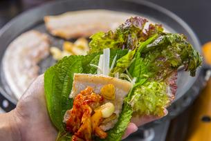 サムギョッサルをサンチュで包んで食べるの写真素材 [FYI04821215]