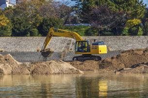 川岸で工事を行う建設機械の写真素材 [FYI04821687]