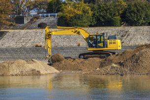 川岸で土砂を掘り起こす油圧ショベルの写真素材 [FYI04821692]