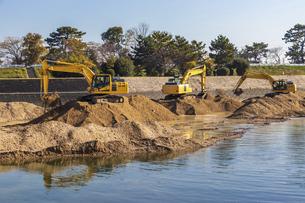 川岸で工事を行う油圧ショベルの写真素材 [FYI04821698]