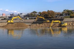 川岸で工事を行う油圧ショベルの写真素材 [FYI04821699]