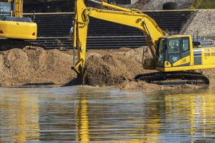 川底の土砂をすくう油圧ショベルの写真素材 [FYI04821701]