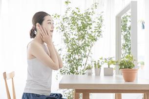 鏡を見て肌の状態をチェックする女性の写真素材 [FYI04822096]