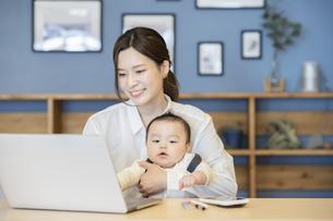 赤ちゃんを抱えてノートパソコンを操作する女性の写真素材 [FYI04822271]
