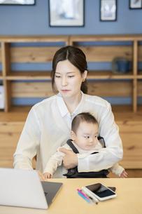 赤ちゃんを抱えてノートパソコンを操作する女性の写真素材 [FYI04822275]