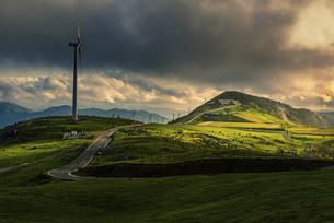 大地に光が満ちる夕方の四国カルストの自然風景 風車の写真素材 [FYI04823324]