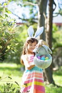 イースターのエッグの入ったバスケットを持っている女の子の写真素材 [FYI04823351]