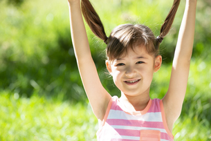 髪の毛を上に持ち上げて笑っている女の子の写真素材 [FYI04823357]