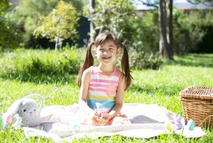 ピクニックマットに座って笑っている女の子の写真素材 [FYI04823362]
