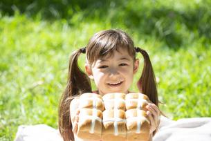 イースターのホットクロスパンを持っている女の子の写真素材 [FYI04823373]