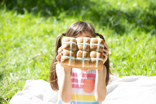 イースターのホットクロスパンを持っている女の子の写真素材 [FYI04823374]