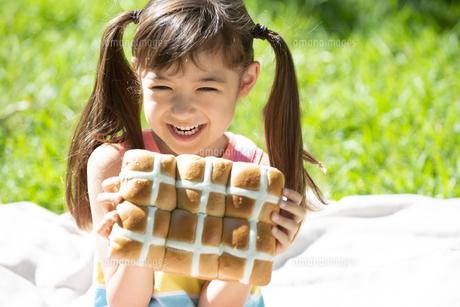 イースターのホットクロスパンを持っている女の子の写真素材 [FYI04823375]