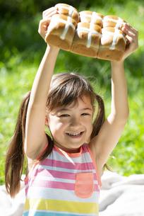 イースターのホットクロスパンを持っている女の子の写真素材 [FYI04823376]