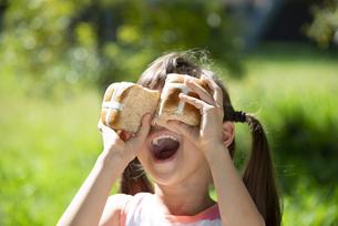 イースターのホットクロスパンを持って笑っている女の子の写真素材 [FYI04823377]