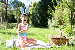 イースターの耳飾りをつけてピクニックをしている女の子の写真素材 [FYI04823381]