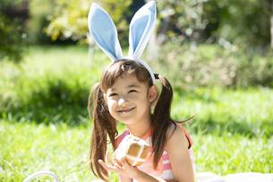 イースターのホットクロスパンを持っている女の子の写真素材 [FYI04823383]