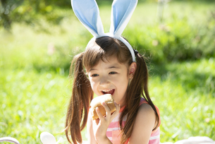 イースターのホットクロスパンを食べている女の子の写真素材 [FYI04823384]
