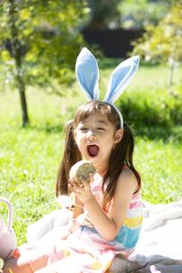 イースターのホットクロスパンを食べようとしている女の子の写真素材 [FYI04823385]