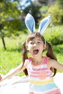 イースターの耳飾りをつけて笑っている女の子の写真素材 [FYI04823390]