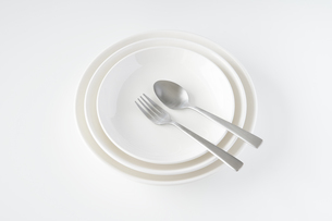 重ねられた白いお皿・フォーク・スプーンの写真素材 [FYI04823406]