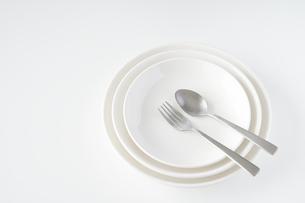 重ねられた白いお皿・フォーク・スプーンの写真素材 [FYI04823407]