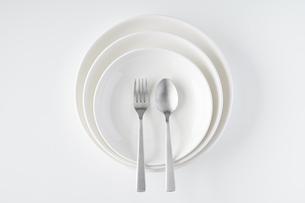 重ねられた白いお皿・フォーク・スプーンの写真素材 [FYI04823409]