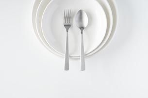 重ねられた白いお皿・フォーク・スプーンの写真素材 [FYI04823410]