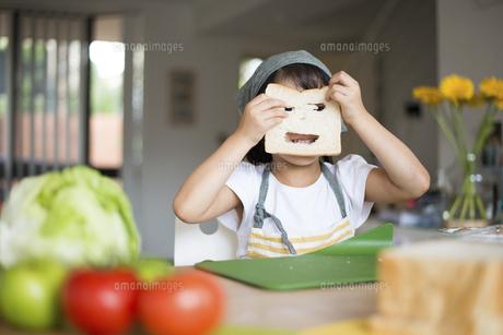 パンに穴を開けて笑っている女の子の写真素材 [FYI04823845]