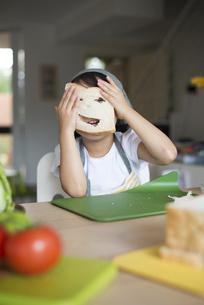 パンに穴を開けて笑っている女の子の写真素材 [FYI04823846]