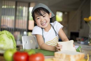 笑顔でサンドイッチを作っている女の子の写真素材 [FYI04823847]