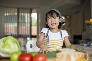 笑顔でサンドイッチを作っている女の子の写真素材 [FYI04823848]
