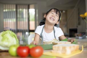 笑顔でサンドイッチを作っている女の子の写真素材 [FYI04823849]
