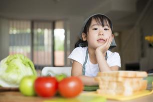 サンドイッチの材料の前で頬杖をついている女の子の写真素材 [FYI04823850]