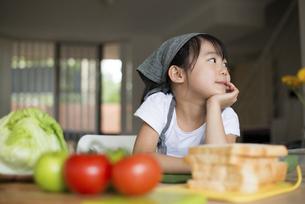 サンドイッチの材料の前で頬杖をついている女の子の写真素材 [FYI04823851]