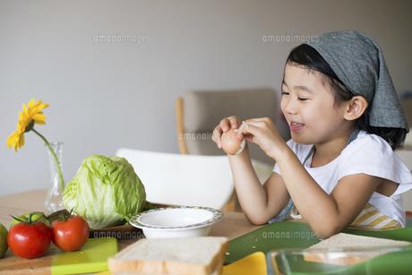エプロン姿でたまごを剥いている女の子の写真素材 [FYI04823852]