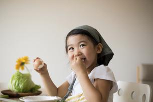 エプロン姿で茹で卵を剥いている女の子の写真素材 [FYI04823853]