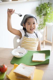 エプロン姿でサンドイッチを作っている女の子の写真素材 [FYI04823855]