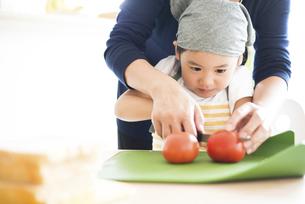 お母さんと一緒にトマトを切っている女の子の写真素材 [FYI04823859]