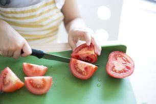 トマトを切っている女の子の手元の写真素材 [FYI04823861]